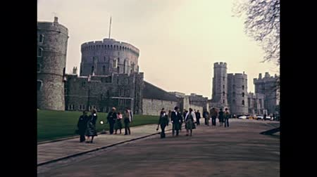 windsor : LONDON, UNITED KINGDOM - CIRCA 1979: tourists visiting Windsor Castle in English county of Berkshire. Historic restored footage in 1970s and people in vintage dress.