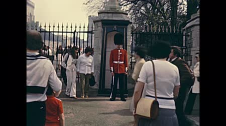 охранять : LONDON, UNITED KINGDOM - CIRCA 1979: British Royal Guard on duty at gate of Windsor Castle. English county of Berkshire. Historic restored footage in 1970s and tourists in vintage dress. Стоковые видеозаписи