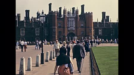 great britain : LONDON, UNITED KINGDOM - CIRCA 1979: Unicorn Gate of Hampton Court Palace, a royal palace in town of East Molesey, Richmond upon Thames. Historic restored footage in 1970s and people in vintage dress. Stock Footage