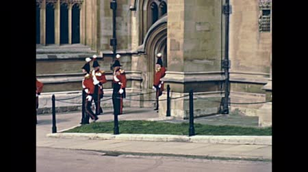охранять : LONDON, UNITED KINGDOM - CIRCA 1979: British Royal Guard on duty marching in Windsor Castle. English county of Berkshire. Historic restored footage in 1970s. Стоковые видеозаписи