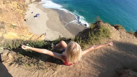 lookout point : Carefree female from promontory looks Pirates Cove, a hidden sandy beach in a small cove on west side of Point Dume on Malibu coast in CA, United States. Caucasian woman in California West Coast.