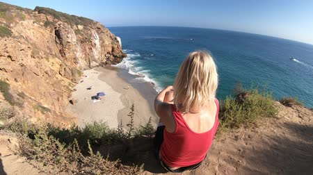 lookout point : Caucasian female looks Pirates Cove promontory Beach from Point Dume promontory on Malibu coast in CA, United States. Carefree woman enjoys California West Coast. Blue sky, sunny.