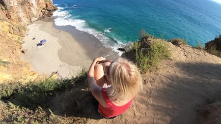 lookout point : California travel destination concept. Lifestyle woman sitting on Pirates Cove promontory, a small cove on west side of Point Dume, Malibu coast in CA, United States. Californian West Coast.