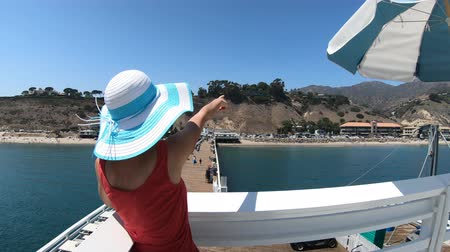 enjoys : Happy girl on top of Malibu Pier in California West Coast, United States. Caucasian girl pointing at popular Carbon Beach in summer. Panorama above wooden pier.