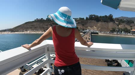 enjoys : Happy woman enjoying at Malibu Pier in California West Coast, United States. Caucasian girl looks Santa Monica Mountains and Surfrider Beach. Aerial view over Pacific Ocean. Summer holidays. Stock Footage