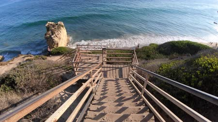 oceano pacífico : Scenic wooden stairway leading down to El Matador State Beach at sunlight. Pacific coast, California, United States. Pillars and rock formations of most photographed Malibu beach, popular spot shot. Stock Footage