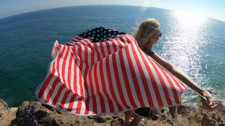 promontory : Woman waving an American flag from Point Dume promontory on Malibu coast in CA, United States. Caucasian female in California West Coast. Freedom and patriotic concept.