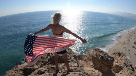 patrik : Woman waving an American flag in the blue sky from Point Dume promontory on Malibu coast in CA, United States above Point Dume Beach.Happy girl in California West Coast. Freedom and patriotic symbol.