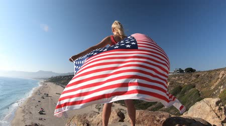 promontory : Freedom and patriotic concept. Woman holding an American flag waving from Point Dume promontory on Malibu coast in CA, United States. Caucasian female in California West Coast. Stock Footage