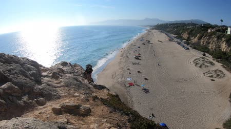 lookout point : Malibu, California, United States - August 7, 2018: man climbing point Dume promontory on Malibu, Pacific Ocean. California West Coast. Aerial view of Pacific coast of Point Dume Beach.
