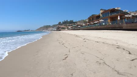 copyspace : Malibu beach houses on popular Carbon Beach or Billionaire Beach for many houses of famous people. Malibu Pier on background. California West Coast landscape. Blue sky, copy space. Summer season. Stock Footage