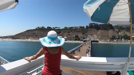 enjoys : Caucasian woman at Malibu Pier in California West Coast, United States. Blonde girl enjoys Santa Monica Mountains and Surfrider Beach. Aerial view over turquoise Pacific Ocean. Summer holidays.