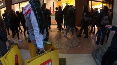 bolognai : BOLOGNA, ITALY- DECEMBER 6, 2018: woman shopping at famous Lego toy store of Bologna. Storefront with Lego shopping bags full of Lego boxes.