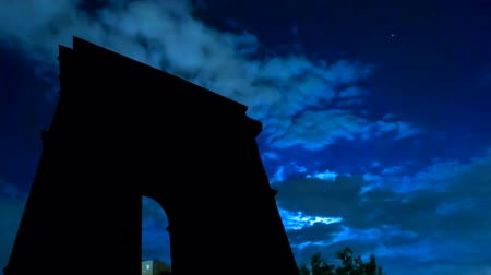 aydınlatmalı : TIME LAPSE: dark sky with moving clouds, the full moon shining and moving clouds at night with Arc De Triomphe backlight. Paris in France. Stok Video