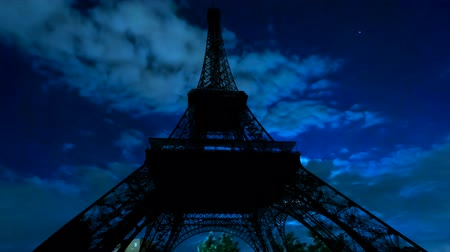 freedom tower : TIME LAPSE: dark sky with moving clouds, the full moon shining and moving clouds at night with backlit Eiffel Tower. Paris in France.