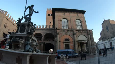 nettuno : Bologna, Italy - December 7, 2018: Neptune 1500s bronze fountain. San Petronio gothic basilica and cathedral, built between the 1400s and 1600s, in Piazza Maggiore central square. Filmati Stock