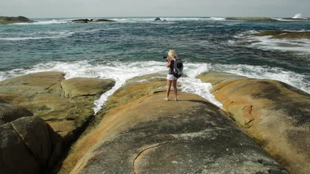 william : Woman photographing on the rocks of Waterfall beach in Denmark, Western Australia. Caucasian tourist looking Great Southern Ocean in William Bay NP. Summer destination in Australia. Stock Footage