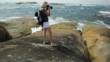 np : Woman photographer pointing her camera at the sea skyline of Waterfall Beach in Denmark, Western Australia. William Bay national park.