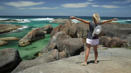 np : Happy woman on the cliffs above elephant-shaped rocks of Elephant Rocks in Western Australia. Young girl looking Great Southern Ocean in William Bay NP. Summer destination in Australia, Albany Region. Stock Footage