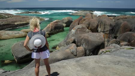 promontory : Woman with hat on top of Elephant Rocks in William Bay National Park, Denmark, Western Australia. Female traveler in Great Southern Ocean coastline. Stock Footage