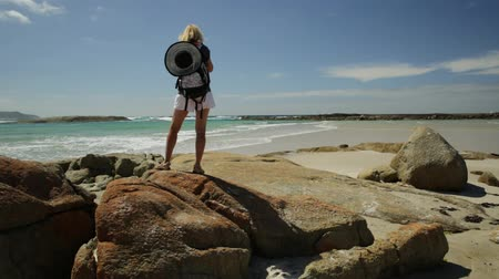 np : Blonde backpacker woman photographer holding her camera at William Bay National Park, Denmark, Western Australia. Tropical destination Madfish Beach surrounded by rocks. Australia summer holidays.