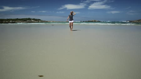 william : Active woman running on seashore of Madfish Bay in William Bay National Park, Denmark region, Western Australia. Carefree girl runs in beach summer day in Australia. Copy space, blue sky.