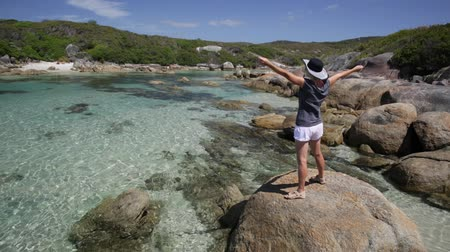 william : Summer season in Denmark coast. Woman with open arms enjoying on the shore with low tide in Madfish Bay, William Bay National Park, Albany region, Western Australia. Stock Footage