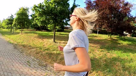pažba : SLOW MOTION blonde woman in tight leggings doing jogging on a city park road. Healthy life concept. Cardio jogging workout girl training outdoor, back side view..