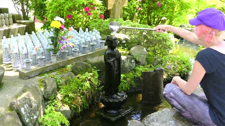traditie : Cinemagraph of a woman worshipping at Jizo Statue. Hase-dera Temple in Kamakura, Japan. Japanese culture concept. Stockvideo