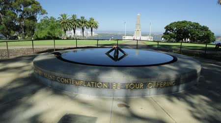 síremlék : Perth, Australia - Jan 3, 2018: Eternal flame of Remembrance and Pool of Reflection with the State War Memorial behind on Mount Eliza in Kings Park. Perth cityscape on background. blue sky