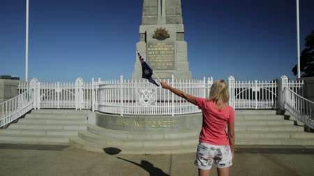 síremlék : Perth, Australia - Jan 3, 2018: National state war memorial cenotaph commemorates Western Australian at Kings Park and Botanic Garden on Mount Eliza. Woman holding an Australian flag in the wind