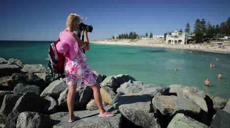 enjoys : Woman photographer photographing the turquoise waters of Cottesloe Beach, Perths most famous town beach, Western Australia. Indian Ocean in summer season with blue sky. Stock Footage