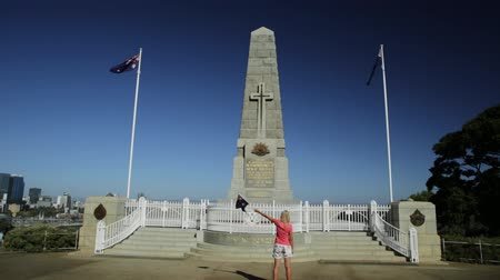síremlék : Perth, Australia - Jan 3, 2018: Woman with an Australian flag at National state war memorial cenotaph commemorates Western Australian at Kings Park and Botanic Garden on Mount Eliza.