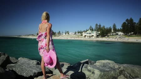 旅行の目的地 : Woman looking at the turquoise waters of Cottesloe Beach, Perths most famous town beach, Western Australia. Girl relaxes on the rocks of the Indian Ocean. Summer season with blue sky. 動画素材
