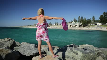 australian landscape : Carefree woman in hat with open arms at Cottesloe Beach, Perths most famous town beach, Western Australia. Tourist girl on the rocks looks at the Indian Ocean. Summer season with blue sky. Stock Footage