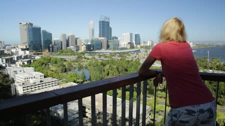 посетитель : Carefree woman overlooking Perth Water, a section of Swan River, and central business district of Perth from Kings Park, the most popular visitor destination in Western Australia. Blue sky, copy space Стоковые видеозаписи