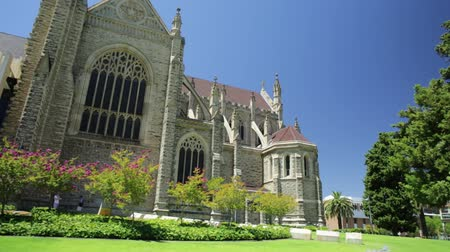 the conception : Side view of St Marys Cathedral with stained glass in Perth, Western Australia. The garden around the Cathedral in neogothic style. Summer season. Blue sky. Landmarks in Perth Capital of WA.