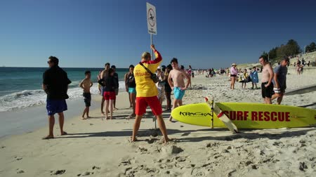 rekin : Cottesloe, Western Australia - Jan 2, 2018: lifeguard placing a no-swimming sign for a shark sighting at Cottesloe Beach in the Perths most famous town beach in the Indian Ocean.