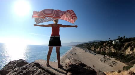 promontory : SLOW MOTION: Woman American flag in the blue sky from Point Dume promontory on Malibu coast in CA, United States above Point Dume Beach.Happy girl in California West Coast. Freedom patriotic concept Stock Footage