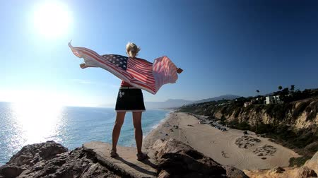 promontory : SLOW MOTION: Woman waving an American flag in the sun from Point Dume promontory on Malibu coast in CA, United States. Caucasian female in California West Coast. Freedom and patriotic concept. Stock Footage