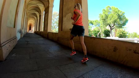 madona : SLOW MOTION: sportwear girl under San Lucas longest archway in the world leading to the San Luca Sanctuary of Bologna city in Italy.