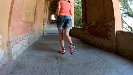 madona : SLOW MOTION: woman legs close up running under San Lucas longest archway in the world leading to the San Luca Sanctuary of Bologna city in Italy. Dostupné videozáznamy