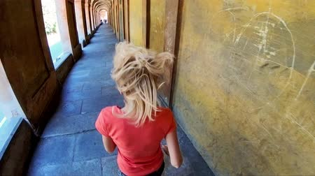 bolognai : SLOW MOTION: woman in pilgrimage, descending the stairway of the San Luca Sanctuary on Bologna city hills, Italy. Aerial view.