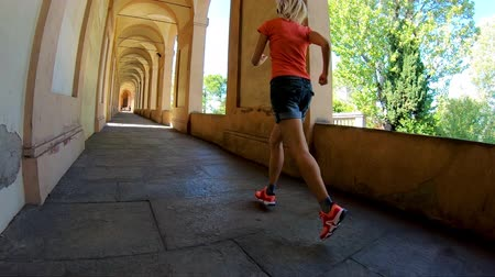oszlopsor : SLOW MOTION: A sportwear woman running under San Lucas portico: the longest porch in the world leading to the San Luca Sanctuary on Colle della Guardia hill. Bologna city of Italy. Stock mozgókép