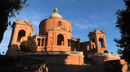 マドンナ : Pronaos and facade of the Sanctuary of Madonna di San Luca at sunset. Basilica church of San Luca in Bologna, Emilia-Romagna, Italy with blue sky. Famous landmark cityscape. 動画素材
