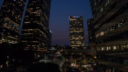 metropolitan area : Los Angeles, California, United States - August 9, 2018: Bottom view of commercial and business office skyscrapers with palms tree in the sky in Los Angeles. Urban cityscape, night view. Stock Footage
