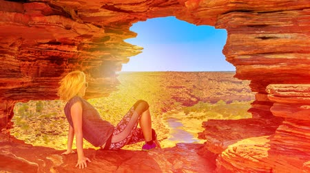 hiking : woman on the rock arch of Natures Window, at sunset on the Murchison River in Kalbarri National Park, Western Australia. Australia travel outback. Stock Footage