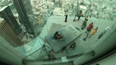 experiência : Los Angeles, California, United States - August 9, 2018: aerial view of tourist woman riding on the Skyslide all-glass at popular US Bank Tower with open-air terrace over the downtown LA. Vídeos