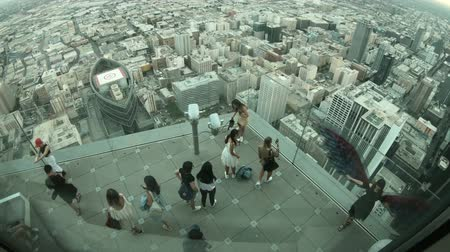 observation deck : Los Angeles, California, United States - August 9, 2018: aerial view of tourists taking photos on panoramic terrace at twilight. People looking at LA Downtown skyline from Oue Skyspace U.S. Bank Tower