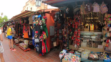 suvenýry : Los Angeles, California, United States - August 9, 2018: tourists shopping in Olvera Street, the oldest part of downtown LA, at El Pueblo in Los Angeles State Historic Landmark since 1953.